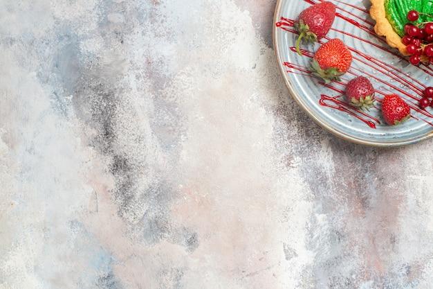 Vista superior delicioso pastel cremoso con frutas en el postre de pastel dulce de galleta de mesa de luz