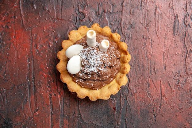Vista superior delicioso pastel cremoso en mesa oscura pastel dulce postre galleta