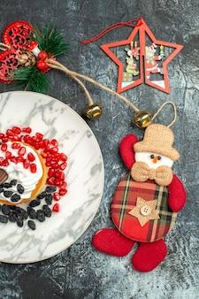 Vista superior delicioso pastel cremoso con pasas y juguetes navideños sobre fondo claro-oscuro