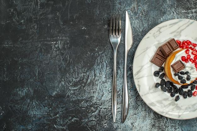 Vista superior delicioso pastel cremoso con pasas y taza de té sobre fondo claro-oscuro