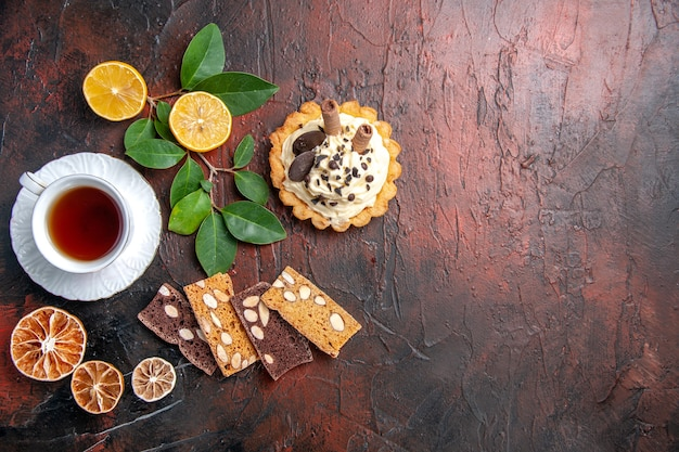 Vista superior delicioso pastel cremoso con taza de té en el postre de pastel dulce de mesa oscura