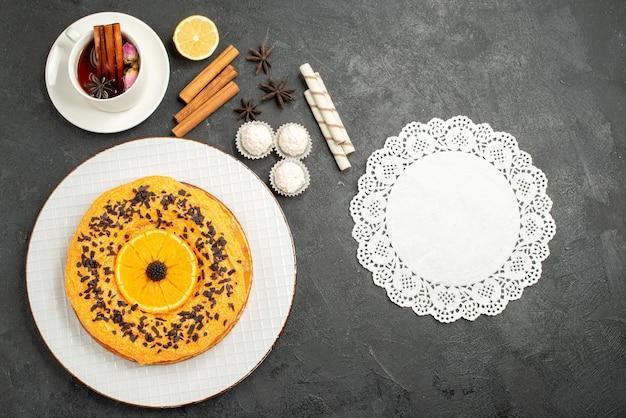 Vista superior delicioso pastel dulce con pequeñas rodajas de naranja y una taza de té en la superficie gris pastel dulce postre galleta té