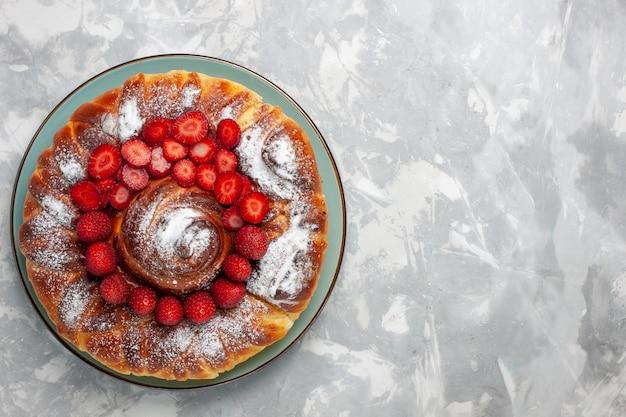 Vista superior del delicioso pastel de fresa con azúcar en polvo en el escritorio blanco