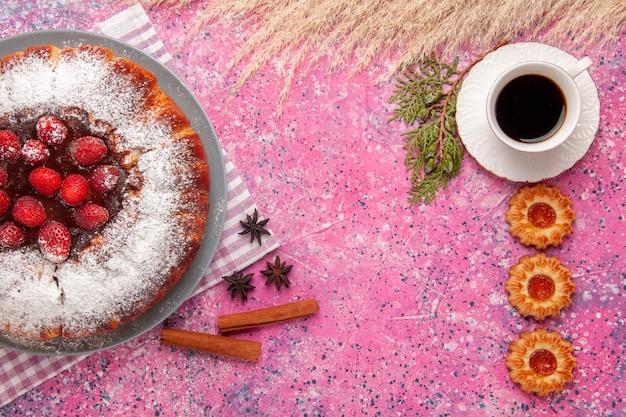 Vista superior delicioso pastel de fresa azúcar en polvo con galletas y una taza de té en el fondo rosa pastel dulce azúcar galleta galleta té