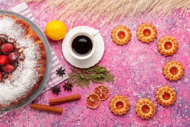 Vista superior delicioso pastel de fresa azúcar en polvo con galletas y té en el fondo rosa claro pastel dulce azúcar galleta galleta té