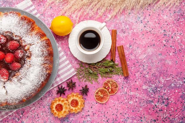 Vista superior delicioso pastel de fresa azúcar en polvo con galletas y té sobre fondo rosa pastel dulce azúcar galleta galleta té