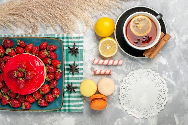 Vista superior delicioso pastel de fresa con fresas frescas taza de té y macarons sobre fondo blanco.