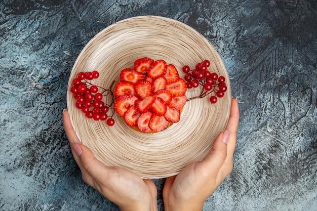 Vista superior delicioso pastel de fresa con frutos rojos en piso oscuro