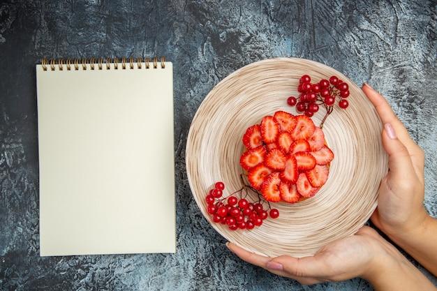 Vista superior delicioso pastel de fresa con frutos rojos sobre fondo oscuro