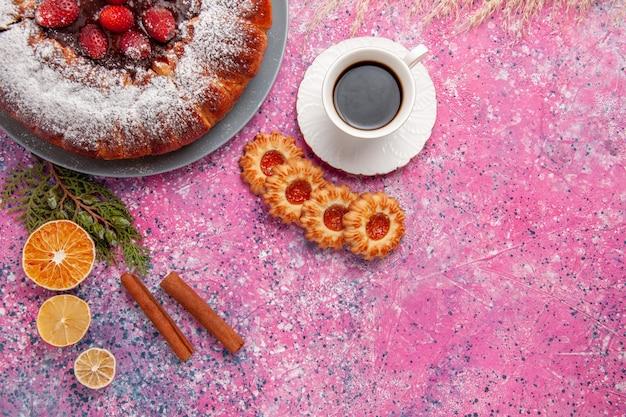 Vista superior delicioso pastel de fresa con galletas y una taza de té en el fondo rosa pastel hornear pastel dulce de azúcar galleta galleta color pastel