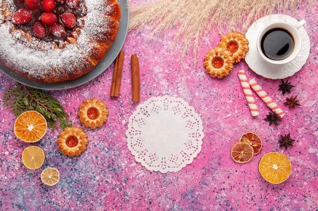 Vista superior delicioso pastel de fresa con galletas y taza de té en el fondo rosa pastel hornear pastel de galleta de galleta de azúcar dulce