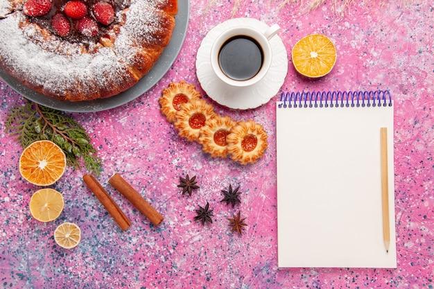 Vista superior delicioso pastel de fresa con galletas y una taza de té sobre fondo rosa claro pastel hornear pastel dulce de azúcar galleta galleta color pastel