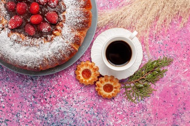 Vista superior delicioso pastel de fresa con galletas y taza de té sobre fondo rosa pastel de azúcar dulce pastel de galletas hornear