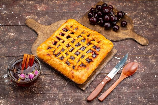 Una vista superior del delicioso pastel de fresa con gelatina de fresa, cerezas y té en el escritorio de madera, pastel, galleta, azúcar