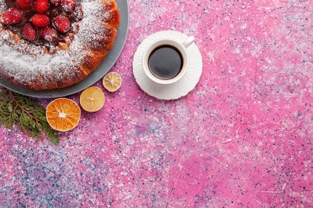 Vista superior delicioso pastel de fresa horneado con azúcar en polvo y té en el pastel de fondo rosa claro pastel de galletas de galleta de azúcar dulce