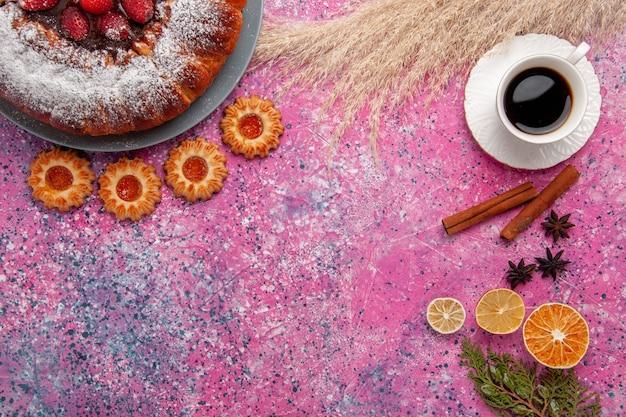 Vista superior delicioso pastel de fresa pastel de azúcar en polvo con galletas y taza de té sobre fondo rosa pastel pastel de galletas de azúcar dulce