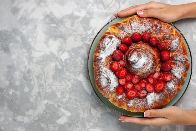 Vista superior delicioso pastel de fresa pastel de azúcar en polvo sobre fondo blanco.