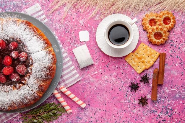 Vista superior delicioso pastel de fresa con taza de té canela y sobre superficie rosa