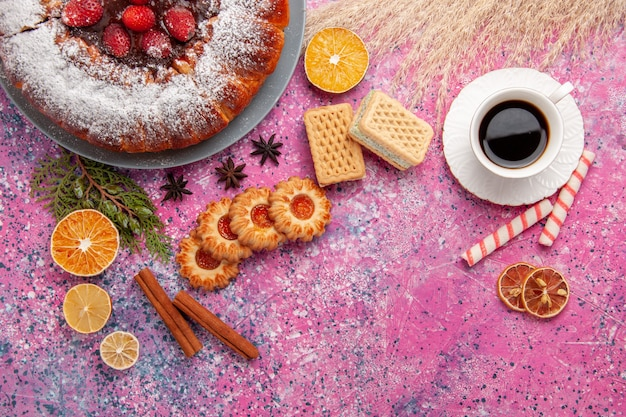 Vista superior delicioso pastel de fresa con té de galletas y gofres en el fondo rosa claro pastel hornear pastel de galleta de galleta de azúcar dulce