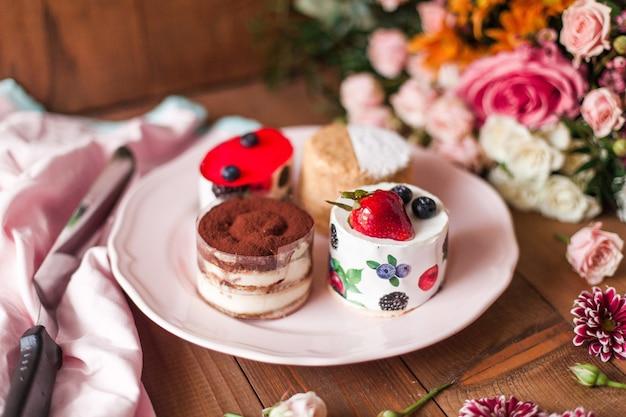 Vista superior de un delicioso pastel con glaseado en la parte superior cerca de coloridas decoraciones florales en una mesa de madera