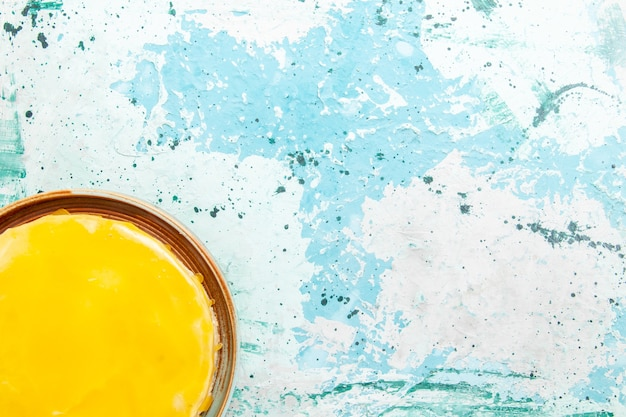Vista superior delicioso pastel con jarabe amarillo sobre fondo azul pastel de galletas hornear galletas dulces té de azúcar