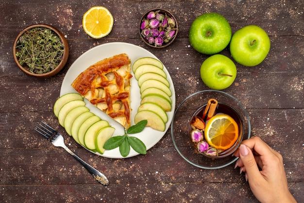 Una vista superior del delicioso pastel de manzana con té, manzanas verdes frescas y limón en el escritorio de madera, pastel, galleta, azúcar