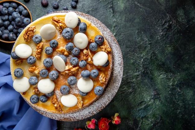 Vista superior delicioso pastel con nueces, arándanos y galletas superficie oscura