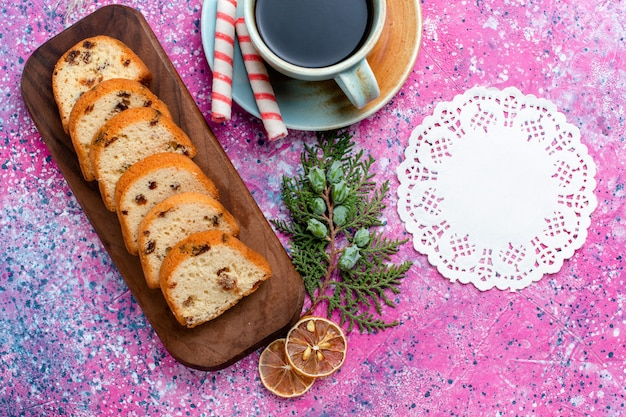 Vista superior delicioso pastel de pasas pastel en rodajas con café en el fondo rosa pastel hornear azúcar galleta dulce galleta