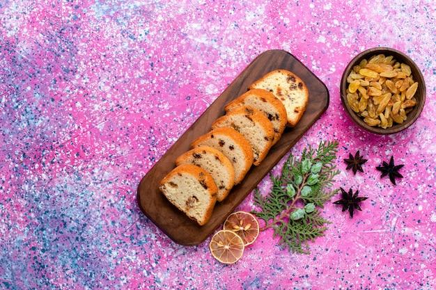 Vista superior delicioso pastel de pasas en rodajas en el escritorio rosa pastel hornear azúcar galleta dulce color de galleta