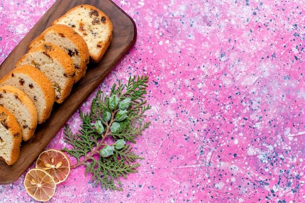Vista superior del delicioso pastel de pasas en rodajas sobre el fondo de color rosa claro hornear pastel de azúcar galleta dulce color de galleta