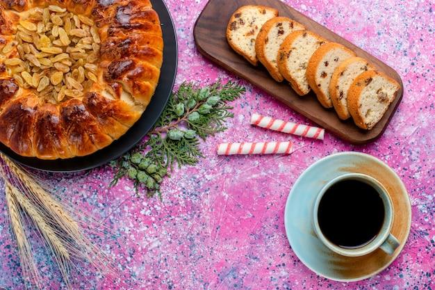 Vista superior del delicioso pastel de pasas con una taza de café sobre fondo rosa hornear pastel de azúcar galletas dulces galletas color