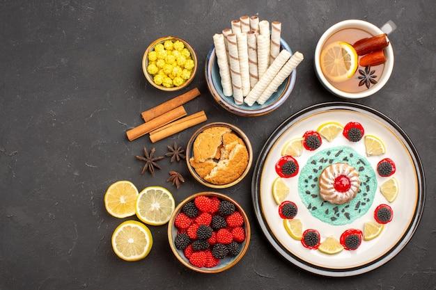 Vista superior del delicioso pastel con rodajas de limón, caramelos y taza de té sobre fondo oscuro, pastel de galletas, frutas, cítricos, galletas dulces.