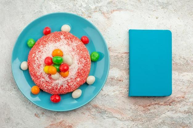 Vista superior del delicioso pastel rosa con caramelos de colores dentro de la placa en un postre de pastel de pastel de color caramelo arco iris de escritorio blanco