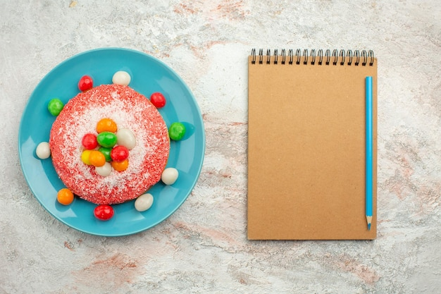 Vista superior del delicioso pastel rosa con caramelos de colores dentro de la placa en la superficie blanca pastel de pastel de color arco iris dulce de postre