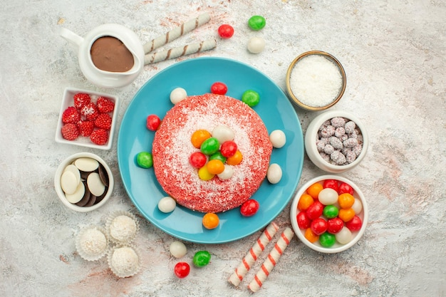 Vista superior del delicioso pastel rosa con caramelos de colores y galletas en la superficie blanca del color del arco iris pastel de postre dulces