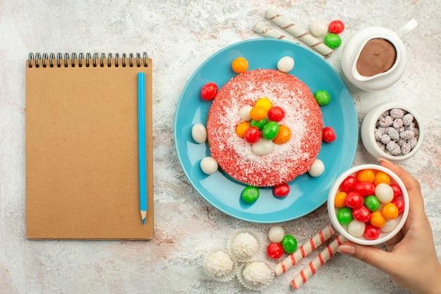 Vista superior del delicioso pastel rosa con caramelos de colores sobre la superficie blanca, postre, pastel de arco iris de color, golosina