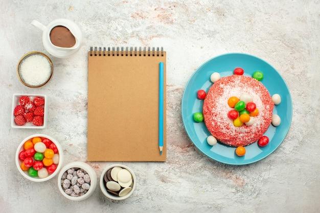 Vista superior del delicioso pastel rosa con caramelos de colores en la superficie blanca clara, color pastel de postre, caramelo de arco iris