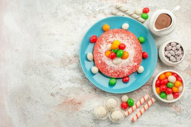 Vista superior del delicioso pastel rosa con caramelos de colores en la superficie blanca, postre, color, golosinas, pastel de arco iris, caramelo