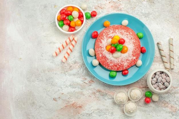 Vista superior del delicioso pastel rosa con caramelos de colores en la superficie blanca, postre, pastel de golosinas de arco iris de color
