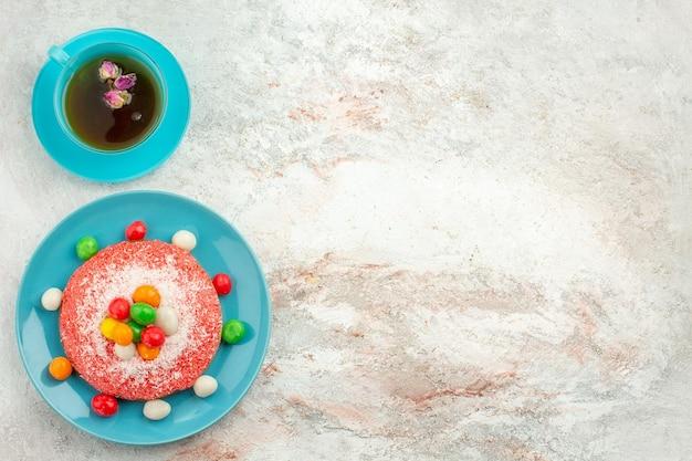 Vista superior del delicioso pastel rosa con caramelos de colores y una taza de té en la superficie blanca pastel de color arco iris pastel postre dulce