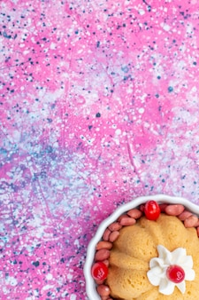 Vista superior del delicioso pastel simple con crema y cacahuetes frescos en piso brillante galleta de pastel dulce nuez de azúcar