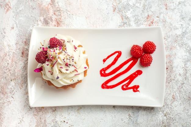 Vista superior delicioso pastelito con crema y frambuesas sobre fondo blanco pastel de té postre crema dulce galleta