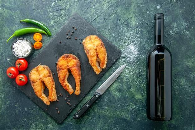 Vista superior delicioso pescado frito en superficie oscura plato ensalada freír carne pimiento mar comida cocinar comida mariscos vino