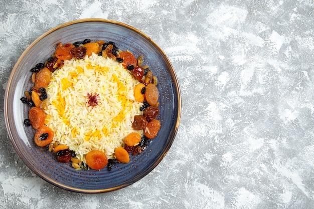 Vista superior delicioso plato de arroz cocido shakh plov con pasas dentro de la placa en blanco