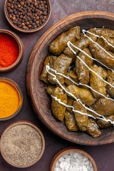 Vista superior del delicioso plato de carne de dolma con diferentes condimentos en un escritorio oscuro, comida, calorías, cena, plato, carne