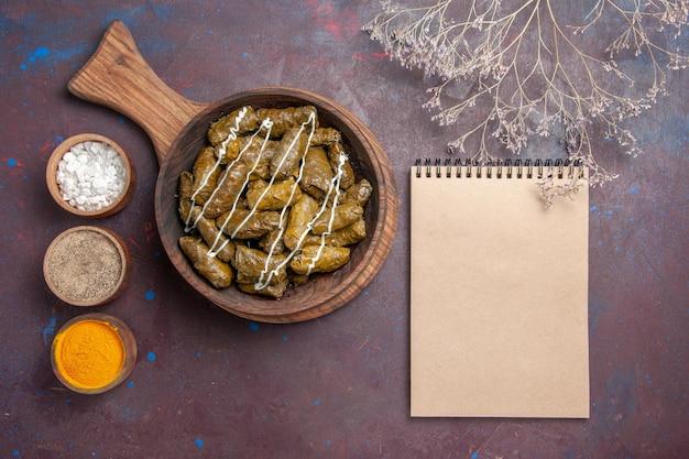 Vista superior del delicioso plato de carne de dolma con diferentes condimentos en el escritorio oscuro plato de cena comida carne calorías