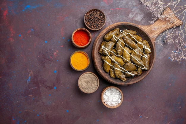 Vista superior del delicioso plato de carne de dolma con diferentes condimentos en el fondo oscuro comida calórica cena plato carne