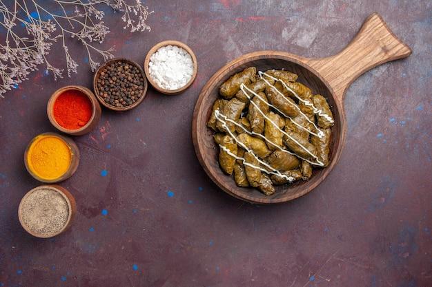 Vista superior del delicioso plato de carne de dolma con diferentes condimentos en el fondo oscuro, comida, cena, plato, carne, calorías