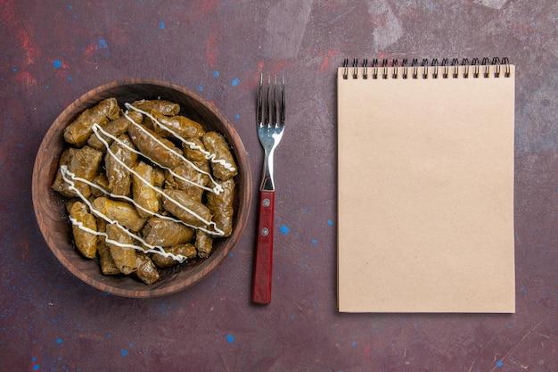 Vista superior del delicioso plato de carne oriental de dolma con hojas y carne molida en el fondo oscuro comida calórica cena plato de aceite carne