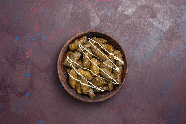 Vista superior del delicioso plato oriental de dolma con hojas y carne molida en el interior sobre un fondo oscuro, aceite, calorías, cena, carne, comida